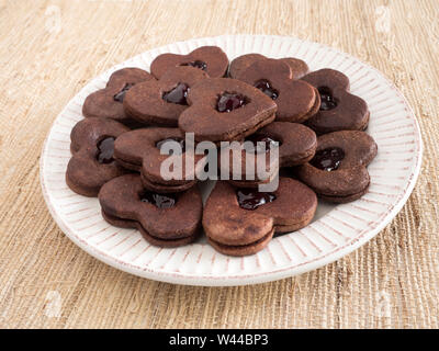 A plate of heart-shaped chocolate sandwich cookies with a layer of jam between the two chocolate cookie layers on a beige plate against a woven placem - Stock Photo