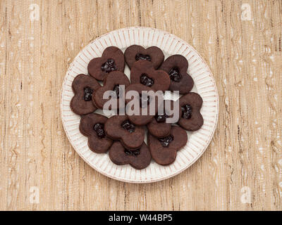 Overhead view of a plate of heart-shaped chocolate sandwich cookies with a layer of jam between the two chocolate cookie layer, against a woven beige - Stock Photo