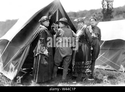 Mary Dimmick Harrison, wife of President Benjamin Harrison and her daughter Elizabeth Harrison Walker with Mrs. Green and probably her daughter, Helen standing at tent of Emergency Services Corps camp where young women were trained in shooting, military drills, hiking and other activities by Army officers, on the estate of Mr. and Mrs. Edward Hewitt, Passaic County, New Jersey, USA, Bain News Service, 1916 - Stock Photo