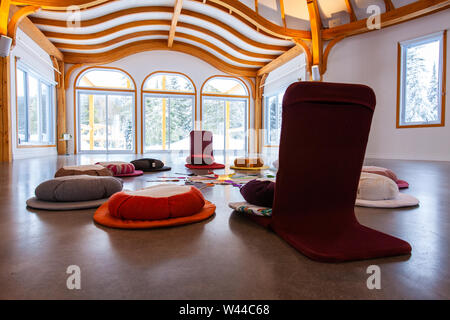 A wide angle view inside a bright, clean, modern room with white walls and exposed beams. Calm and peaceful setting for meditation in circle. - Stock Photo