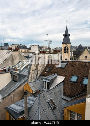 A view of rooftops from a 7th floor apartment in the 5th arrondisement of Paris shows a variety of buildings, heights, textures, materials and color - Stock Photo