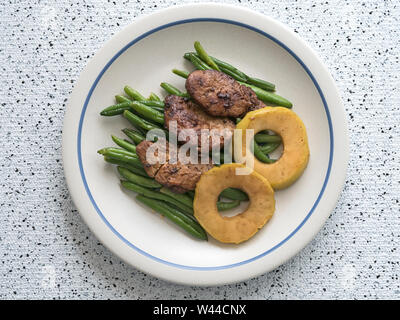 Overhead view of an individual serving of sauteed pork medallions served over a bed of garlic green beans and accompanied with glazed apple rings - Stock Photo