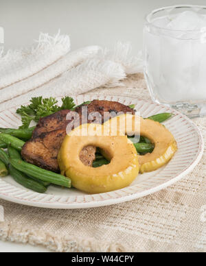 Individual serving of garlic green beans topped with seasoned meat medallions and glazed apple rings - Stock Photo