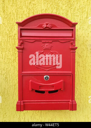 Red metal mailbox on a yellow wall - Stock Photo