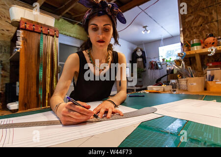 A closeup view of a lady fashion designer using technical drawing equipment to create clothes illustration in retro studio. - Stock Photo