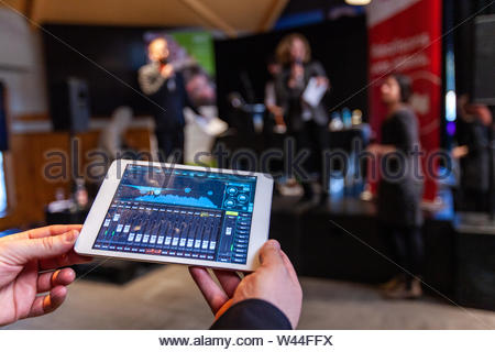 A first person view of a sound technician using a tablet app as speakers are seen blurred in background, prepare to give a presentation on stage - Stock Photo