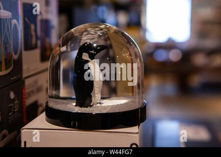 A close-up view of a festive snow globe with a penguin figurine inside, ornamental christmas decoration for sale in small local home wares store. - Stock Photo