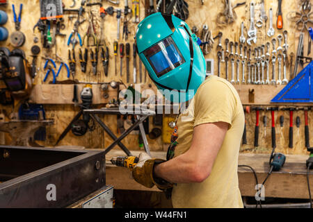 A blacksmith looks towards camera whilst wearing a protective welding mask and drilling steel. Skilled tradesman wears protective gear inside workshop - Stock Photo
