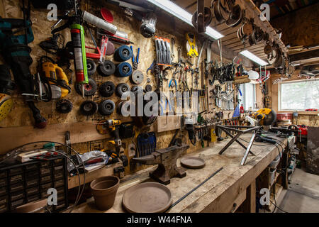 A variety of metalwork tools including abrasive cutting discs hang over a workbench inside a garage. Handy tools neatly organized above a workstation. - Stock Photo