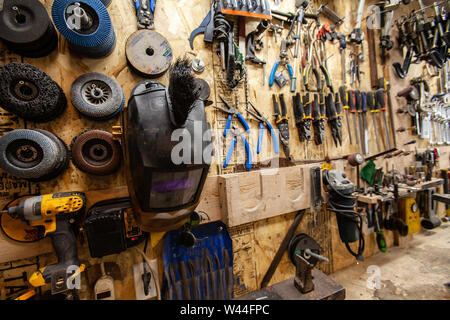 A closeup view on a selection of blacksmith's tools, neatly organized, hanging on a wall inside a workshop. - Stock Photo