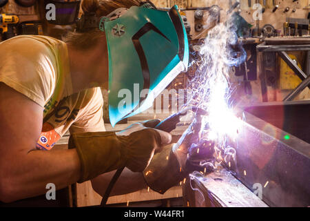 A closeup and side profile of a metalworker using a gas metal arc welding machine to join two pieces of steel. Skilled worker operates welding machine - Stock Photo