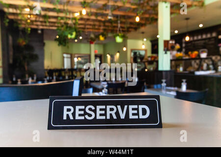 A table reservation sign is seen close-up inside an eco-friendly establishment. Blurry green foliage and decor is viewed in background with copy space to top. - Stock Photo