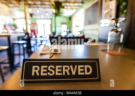 A table reservation sign is viewed close up inside a trendy bistro, place settings and decor are blurred out in the background with copy space to the top. - Stock Photo