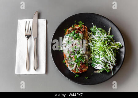 A top down view of freshly prepared tuna steak and green salad, served on a modern black plate against a grey table, fine dining in restaurant. - Stock Photo
