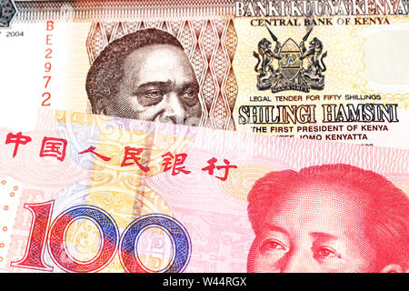 A fifty Kenyan shilling note, in macro, close up with a red one hundred yuan renminbi note featuring a portrait of Mao Tse Tung - Stock Photo