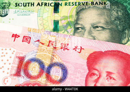 A green ten rand note from South Africa close up in macro with a red one hundred yuan renminbi bank note from the People's Republic of China - Stock Photo