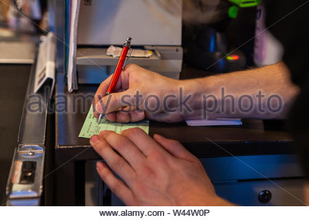 A closeup view of a Caucasian person filling in a booking form in a professional work environment, ticket used in hotels and restaurants. - Stock Photo
