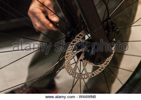 A close up view of the braking system on a mountain bike, metal plate and cables are seen in detail, a blurry mechanic stand behind the spokes. - Stock Photo