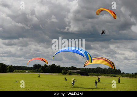 Paramotoring club with kiting practise on the ground with and without motor and an airborne pilot flying by in Hungerford England - Stock Photo