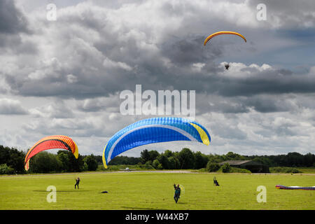 Paramotoring club with kiting practise on the ground with and without motor and an airborne pilot coming in for a landing in Hungerford England - Stock Photo