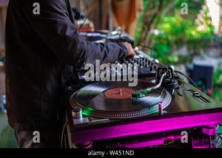 A music DJ is viewed closeup, operating an old-fashioned vinyl turntable during an eclectic music festival outdoors, using hands to control knobs. - Stock Photo