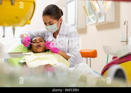 Concentrated serious middle-aged female doctor holding dental instruments - Stock Photo