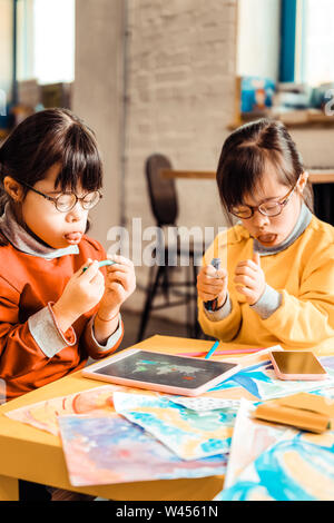 Curious little girls with mental issues pulling out tongues - Stock Photo
