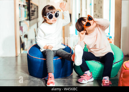 Peaceful young sisters with down syndrome wearing light sweaters - Stock Photo
