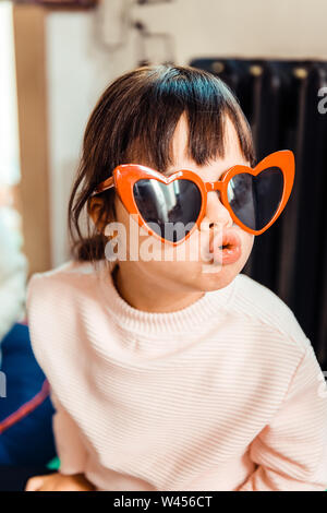 Fashionable little girl with long bangs wearing light sweater - Stock Photo