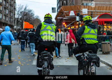 Two policemen are seen from the rear, riding bicycles during a demonstration by environmentalists, protestors are seen in the background on an urban street - Stock Photo