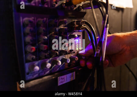 A close up view on the hand of a music producer using audio equipment backstage, turning volume knob on instrument panel with copy space on the right. - Stock Photo