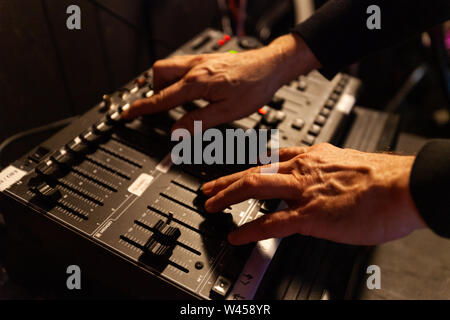 A closeup view on the hands of a sound technician using an electronic control panel with balancing levers during a music production, with copy-space on the left - Stock Photo