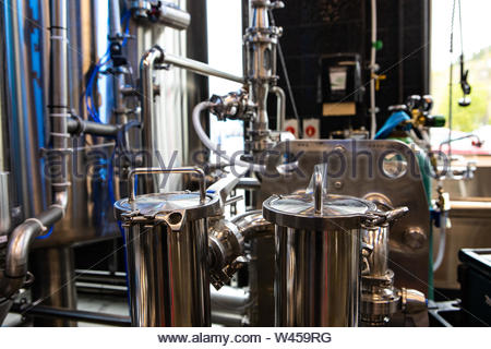 A closeup view of brewing industry machines inside a large beer factory. Production and fermentation process with copy-space towards the top. - Stock Photo
