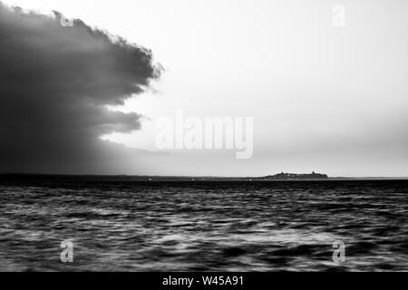 Beautiful view of Trasimeno lake (Umbria, Italy) at sunset, with empty sky and a big cloud on the left - Stock Photo