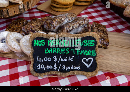 A closeup view of a French price sign, saying our marvelous soft bars, on a home baker's stall during a fair for local producers, baked goods seen in background - Stock Photo