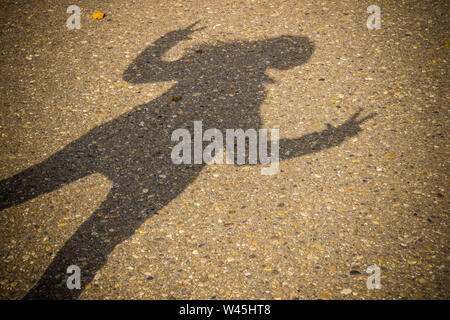Shadow of a standing woman holding two arms and fingers up - Stock Photo