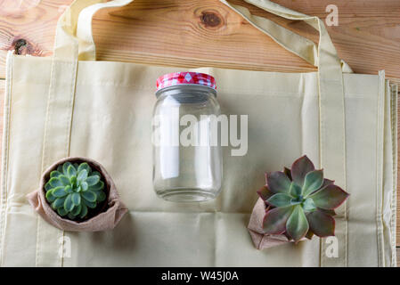 World free of plastic.Green products-bag made from bamboo or reuse, succulent and glass jar on nature wood background. - Stock Photo