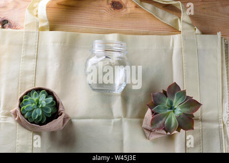 World free of plastic.Green products - bag made from bamboo or reuse, succulent and glass jar on nature wood background. - Stock Photo