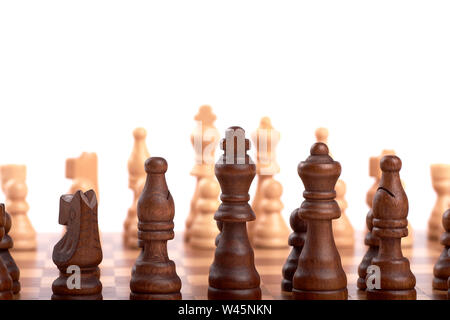 Row of white and black wooden chess pieces on a chessboard, with selective focus, isolated on white background.