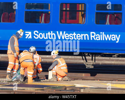 Clapham Junction, London, UK; 14th February 2019; Group of Rail Workers Working Trackside With South Western Railway Train Behind - Stock Photo