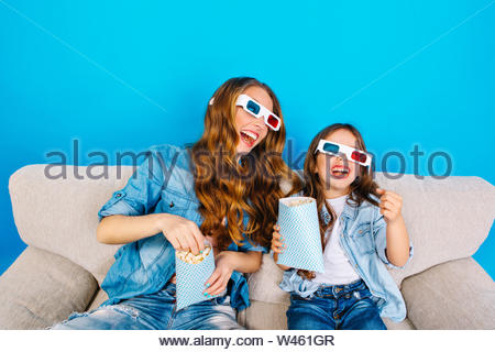 Crazy fun of joyful mother with funny daughter in 3D glasses on couch eating popcorn on blue background. Wearing jeans clothes, expressing positivity, watching movie mum together with child - Stock Photo