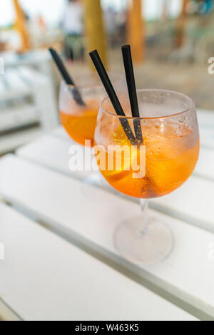 Delicious classic iced aperol spritz cocktail with ice cubes on a hot tropical beach in summer sunshine