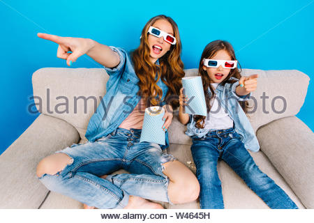 Fashionable joyful mother and her daughter in jeans clothes eating popcorn, watching movie in 3D glasses on couch isolated on blue background. Expressing crazy happiness, true emotions - Stock Photo