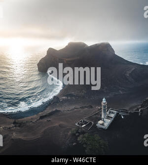 View over Capelinhos volcano, lighthouse of Ponta dos Capelinhos on western coast on Faial island, Azores, Portugal with a dramatic sunset and strong - Stock Photo