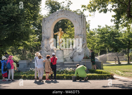Tourists at Johann Strauss memorial site, while gardeners maintain grounds, Stadtpark, a 19th century public park in Vienna, Austria. - Stock Photo
