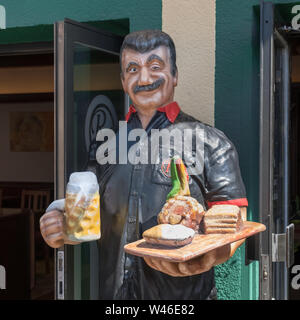 A mannequin with food and drink outside a restaurant at Prater amusement park, Vienna, Austria. - Stock Photo