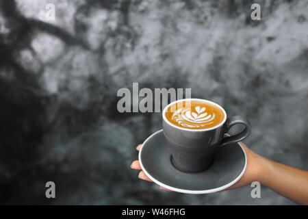 Woman holding in hand gray cup of fresh cappuccino on background of gray concrete cement textured wall. Trendy hipster cafe design.