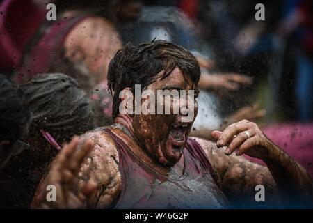 Swansea, Wales, UK. 20th July 2019 Pictured are fundraisers during the Cancer Research UK's Pretty Muddy event in Swansea, South Wales on Saturday. The participants, mainly women, scrambled over a number of muddy challenges on the 5k course in the cities Singleton Park, raising thousands of pounds for the charity. Credit : Robert Melen/Alamy Live News. - Stock Photo