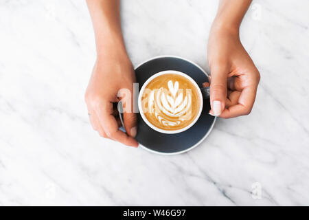Woman hands holding gray cup of fresh cappuccino with classic latte art on white marble table trendy background. Empty place for text, copy space. Cof