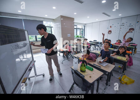 (190720) -- HAINING, July 20, 2019 (Xinhua) -- A science class is given as part of a summer camp organized by a local company for the children of its migrant workers in Haining, east China's Zhejiang Province, July 20, 2019. Running for 40 days starting from mid-July, the summer camp invites 180 children whose parents work for the company away from home and thus offers them a chance for family reunion. Besides, the children can expect an enriched summer life here by taking academic, etiquette and sports courses given by university volunteer tutors. (Xinhua/Xu Yu) - Stock Photo